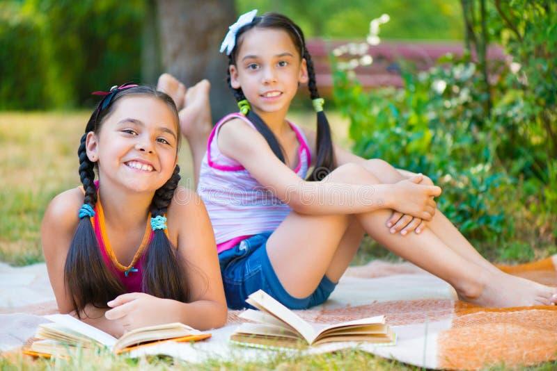 Irmãs latino-americanos felizes que leem no parque imagens de stock