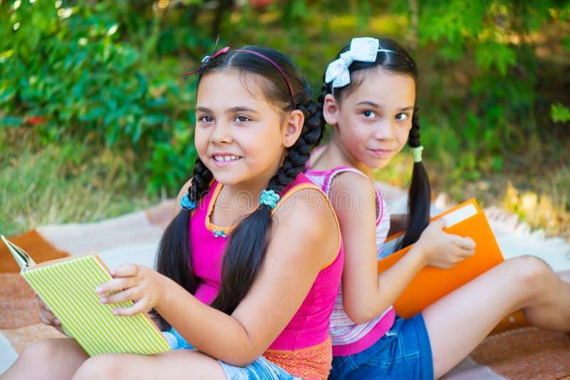 Irmãs latino-americanos que leem no parque do verão imagem de stock