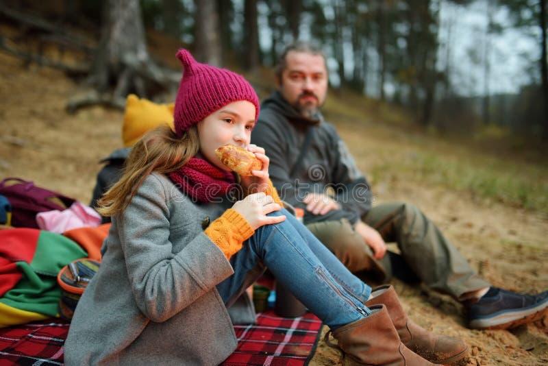 Irmãs mais nova bonitos e seu pai que têm o piquenique por uma fogueira no dia frio do outono Crian?as que t?m o divertimento no  imagem de stock