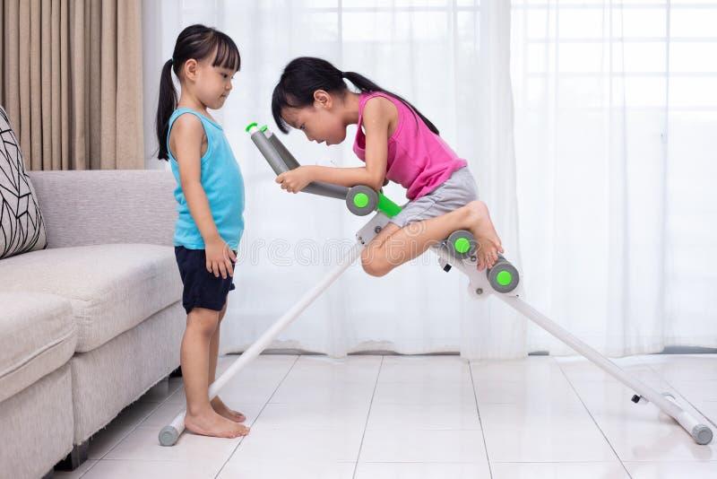 Irmãs mais nova chinesas asiáticas que jogam a máquina do exercício no livi foto de stock