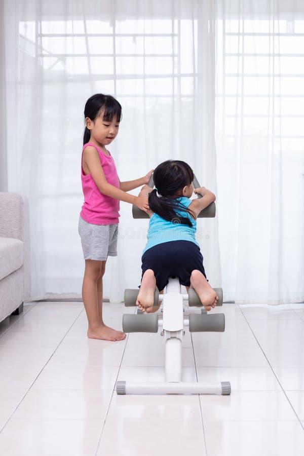 Irmãs mais nova chinesas asiáticas que jogam a máquina do exercício no livi imagem de stock
