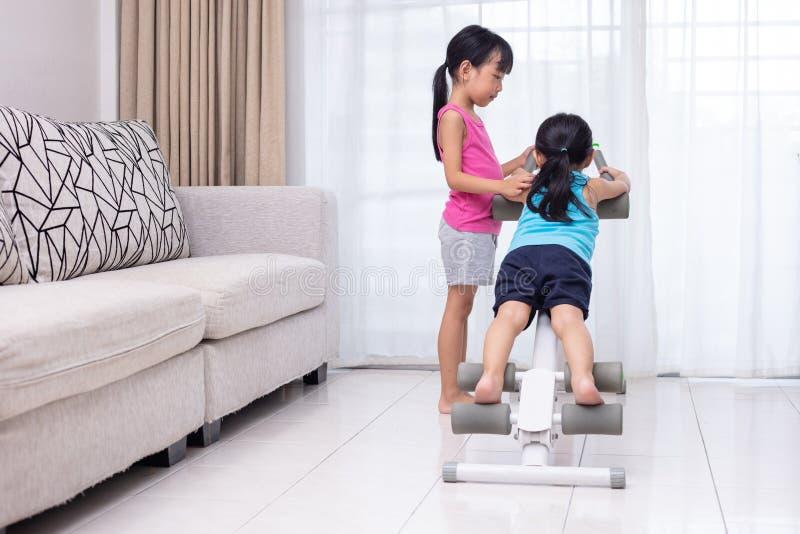 Irmãs mais nova chinesas asiáticas que jogam a máquina do exercício no livi fotos de stock