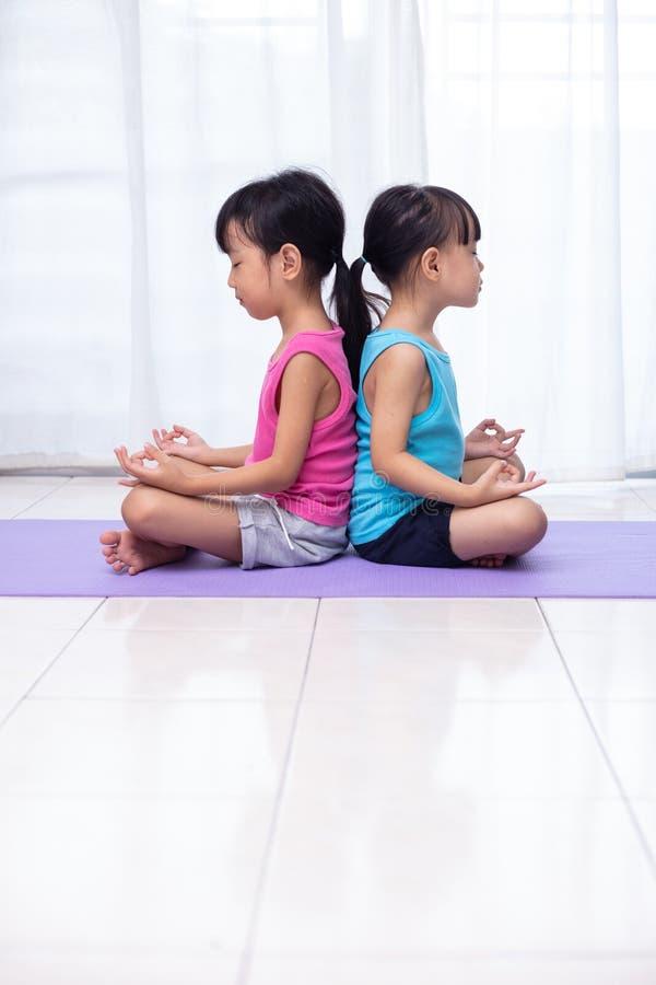 Irmãs mais nova chinesas asiáticas que praticam a pose da ioga em uma esteira fotografia de stock royalty free