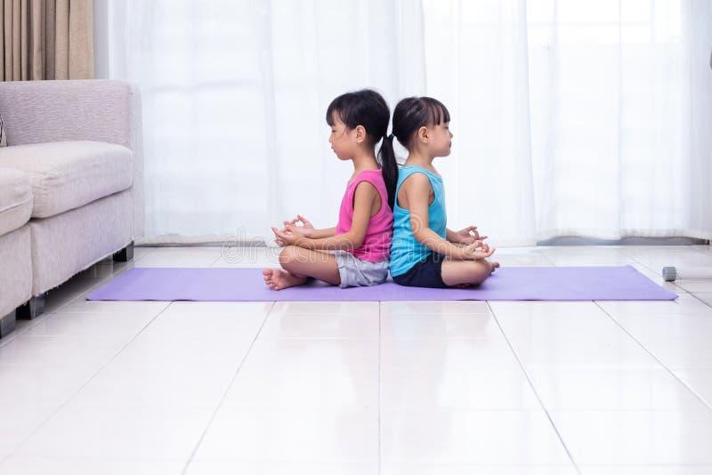Irmãs mais nova chinesas asiáticas que praticam a pose da ioga em uma esteira fotos de stock royalty free