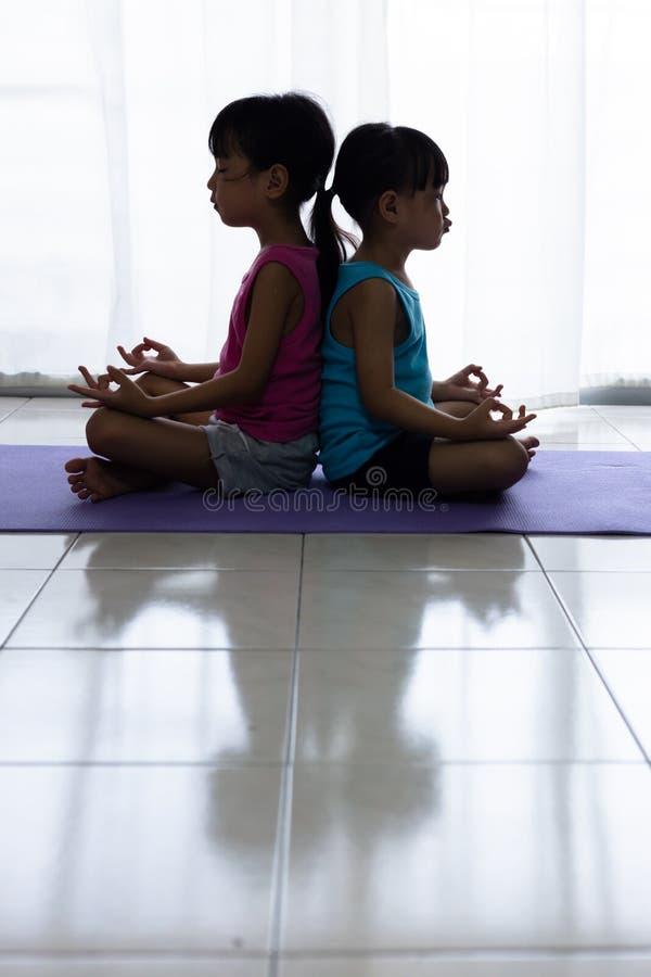 Irmãs mais nova chinesas asiáticas que praticam a pose da ioga em uma esteira foto de stock royalty free