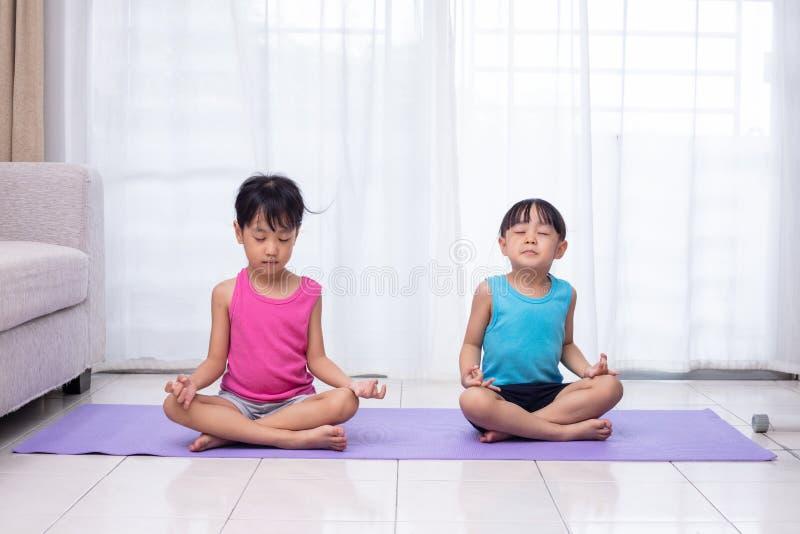 Irmãs mais nova chinesas asiáticas que praticam a pose da ioga em uma esteira fotos de stock