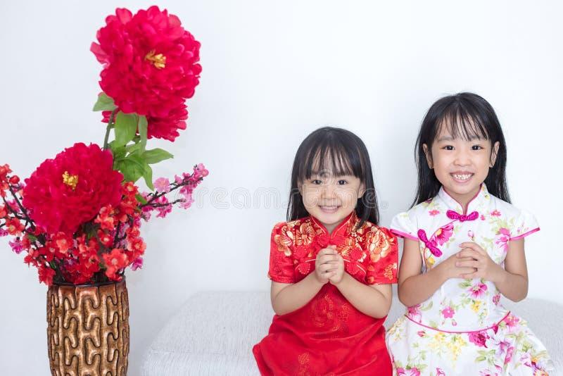 Irmãs mais nova chinesas asiáticas que vestem o cheongsam com ges do cumprimento fotografia de stock