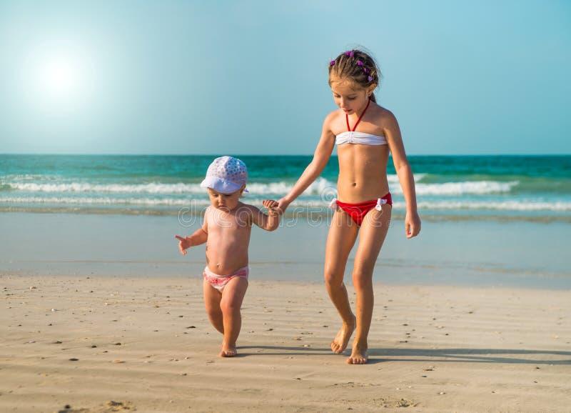 Irmãs mais nova que andam ao longo da praia fotografia de stock