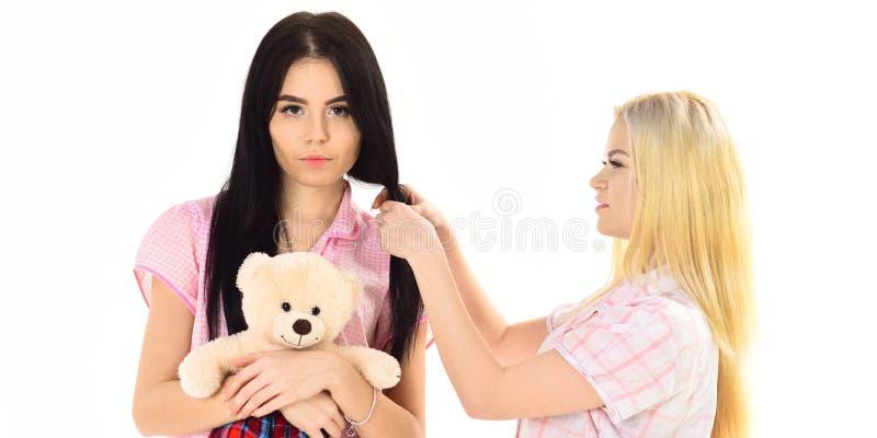 Irmãs, melhores amigos nos pijamas que fazem a trança, penteado As senhoras nas caras de sorriso com o urso do brinquedo do luxuo fotos de stock royalty free