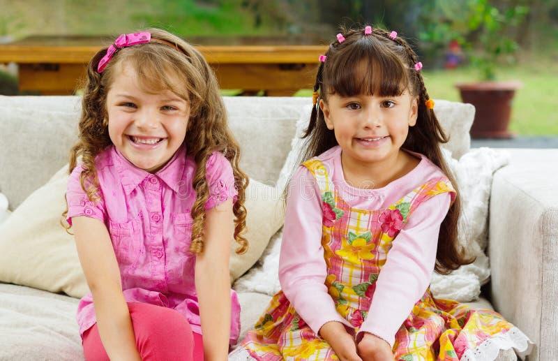 Irmãs morenos das crianças que sentam-se felizmente no branco fotos de stock royalty free