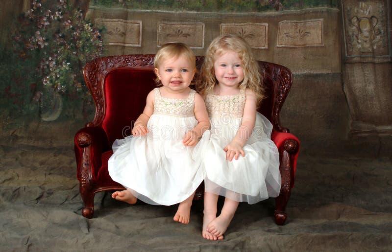 Irmãs no sofá imagem de stock