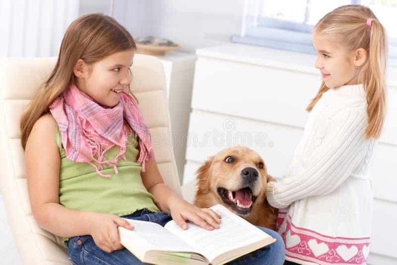 Irmãs pequenas com cão de animal de estimação em casa foto de stock royalty free