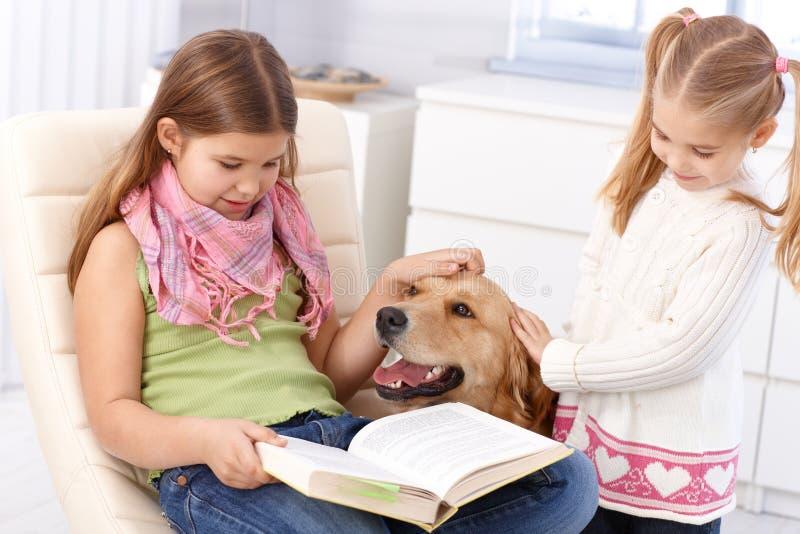 Irmãs pequenas com cão em casa fotografia de stock