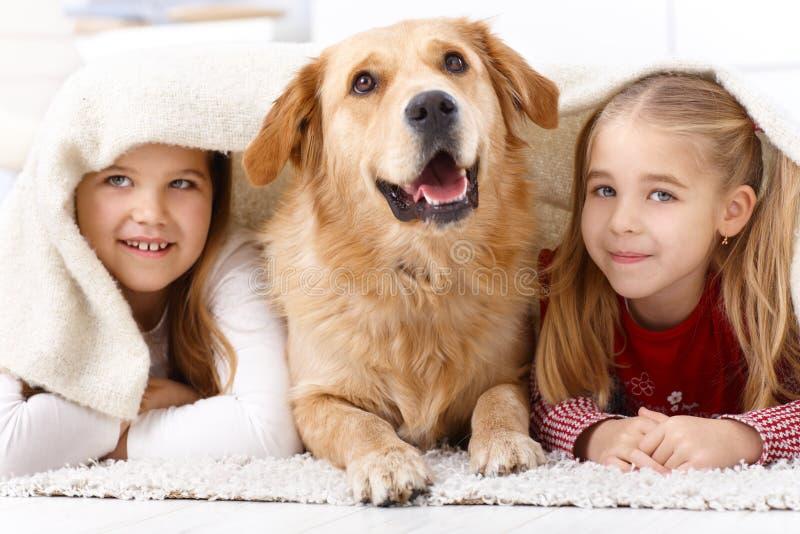 Irmãs pequenas e cão de animal de estimação em casa que sorri imagens de stock royalty free
