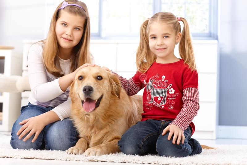 Irmãs pequenas que fondling o cão em casa imagens de stock