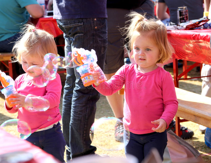 Irmãs pequenas que jogam com bolhas no festival África do Sul imagens de stock royalty free