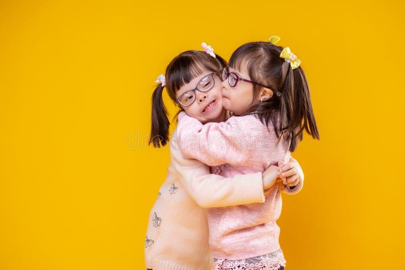 Irmãs positivas de encantamento com a anomalia do cromossoma que abraça-se fotografia de stock royalty free