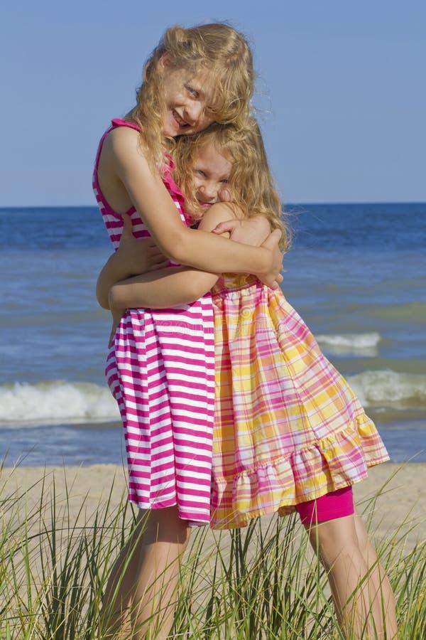 Irmãs que abraçam na praia. foto de stock royalty free