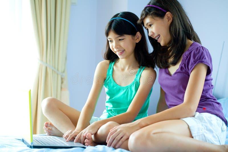 Irmãs que compartilham de um portátil no ambiente familiar fotografia de stock royalty free