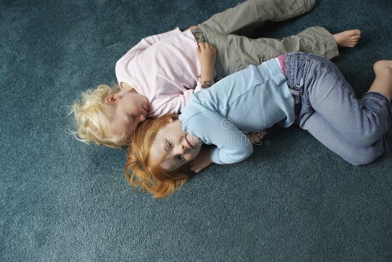 Irmãs que encontram-se no tapete em casa imagem de stock