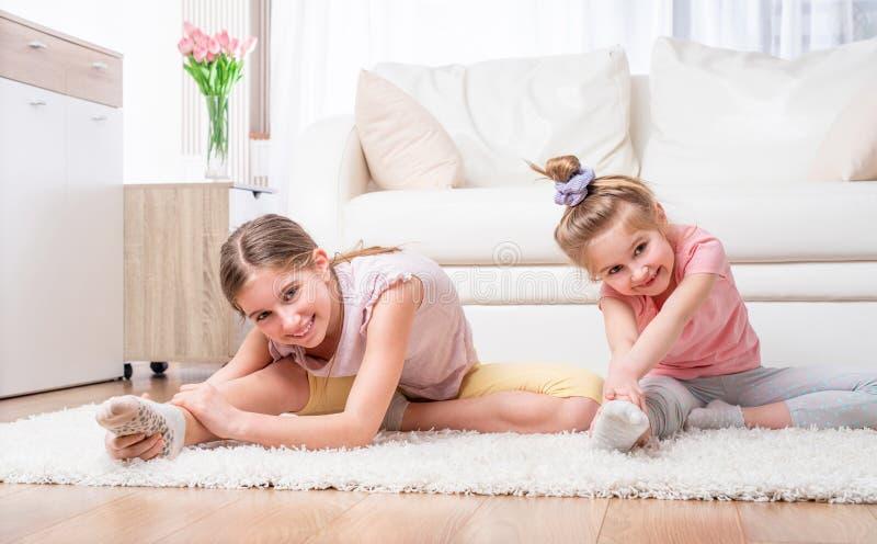 Irmãs que esticam no assoalho fotografia de stock royalty free