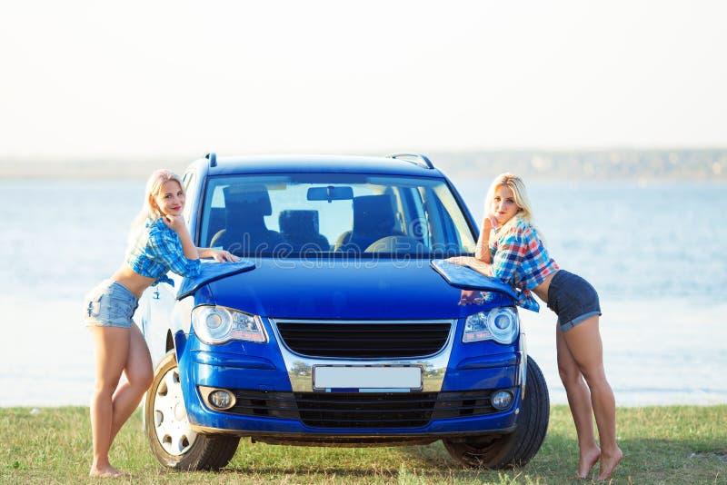 irmãs que levantam ao lado de um carro lavado fotos de stock royalty free