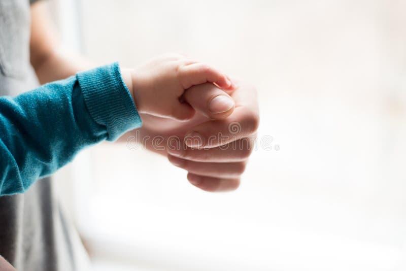 Irmãs que prendem as mãos entregue o bebê de sono na mão do close-up do pai Mãos no fundo branco fotografia de stock