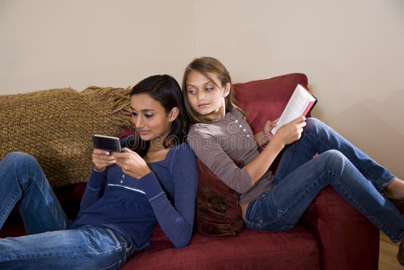 Irmãs que relaxam junto em casa no sofá imagens de stock