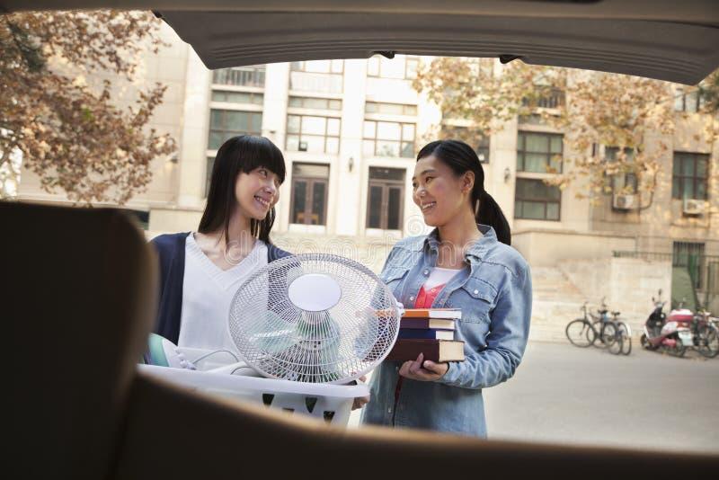 Irmãs que sorriem e que movem-se no dormitório na faculdade fotos de stock royalty free