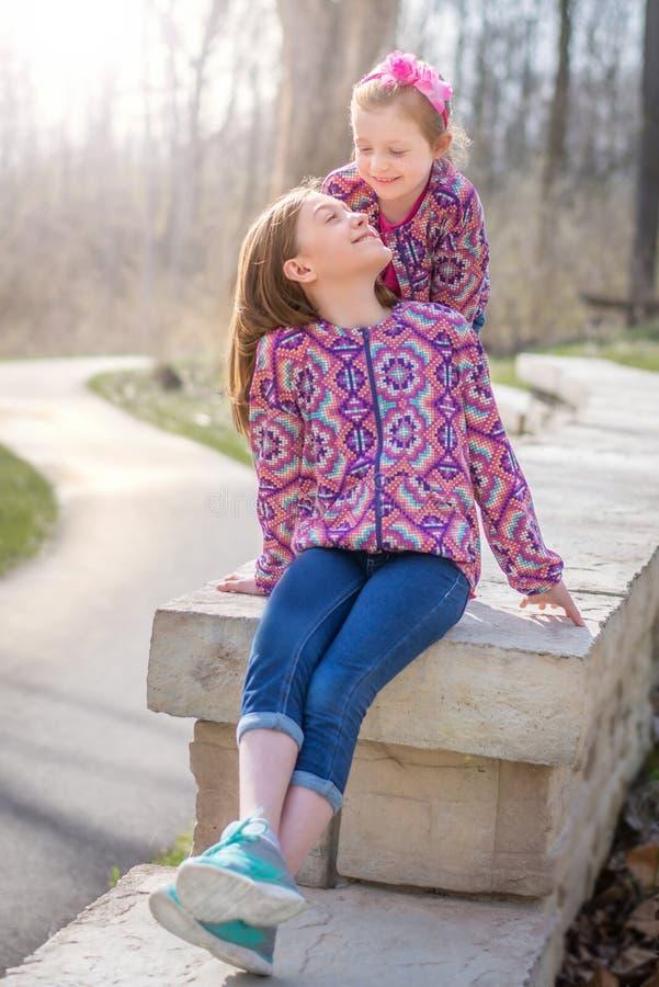 Irmãs que sorriem em se na parede de pedra fotografia de stock