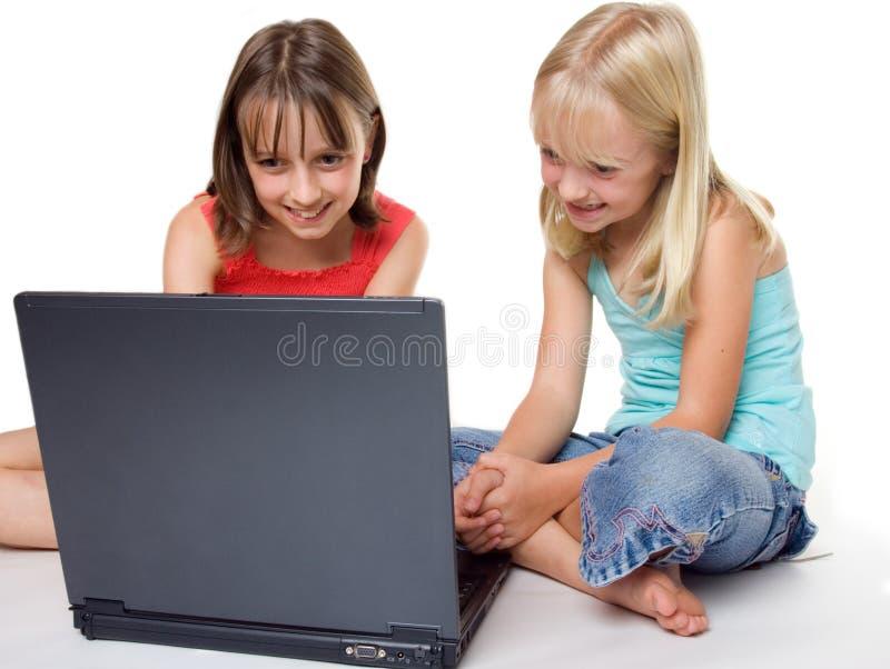 Irmãs que usam um portátil fotografia de stock royalty free