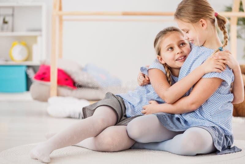 Irmãs que vestem o aperto azul das camisas foto de stock royalty free