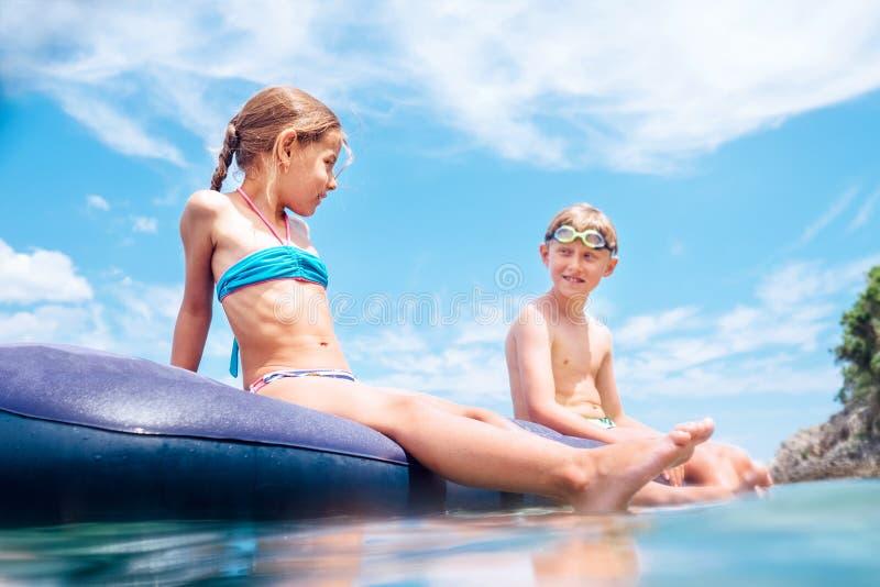 A irm? e o irm?o, tiverem o divertimento quando nadada no colch?o infl?vel no mar Tempo descuidado da inf?ncia foto de stock