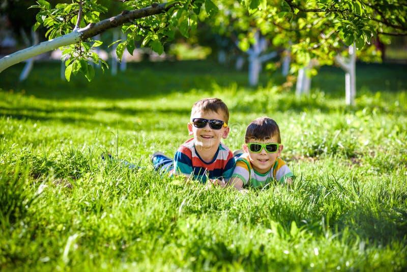 Irm?o de sorriso feliz do irm?o do menino que relaxa na grama Feche acima da vista com espa?o da c?pia fotos de stock