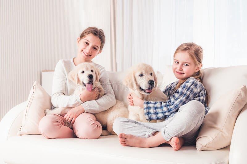 Irm?s de sorriso que sentam-se com cachorrinhos fotografia de stock