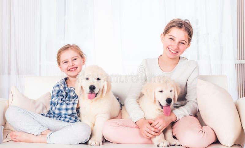 Irm?s de sorriso que sentam-se com cachorrinhos foto de stock royalty free