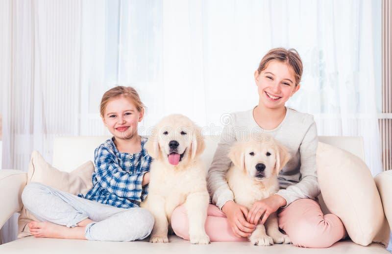 Irm?s de sorriso que sentam-se com cachorrinhos fotos de stock royalty free