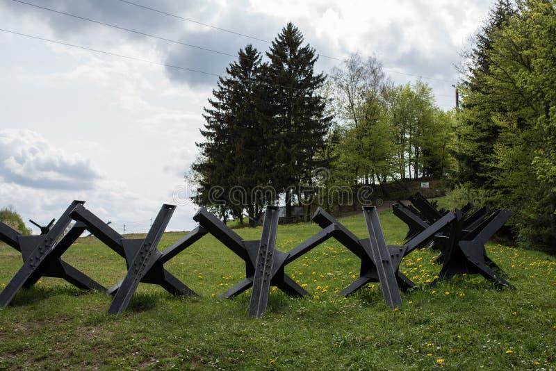 Iron Antitank fence at the battlefield. Old Antitank iron fence at the battlefield near old concrete bunker stock photos