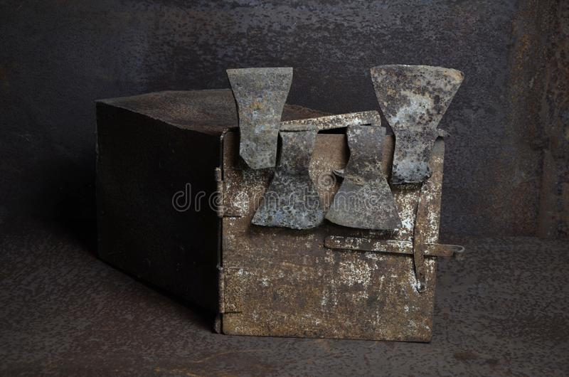 Iron axes, hung on the iron box. With overhead light stock photography