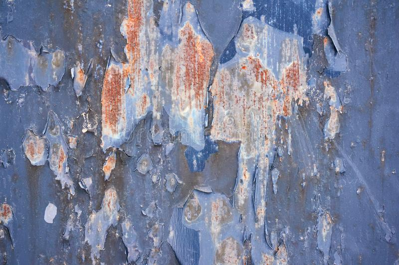 Iron background painted blue paint with cracks scratches and rust. Steel background. Abstract background stock photography