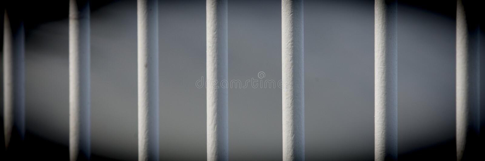 Iron bars, prisoners behind are locked up. Safety first, prison iron bars keep burglars in the cell royalty free stock photos