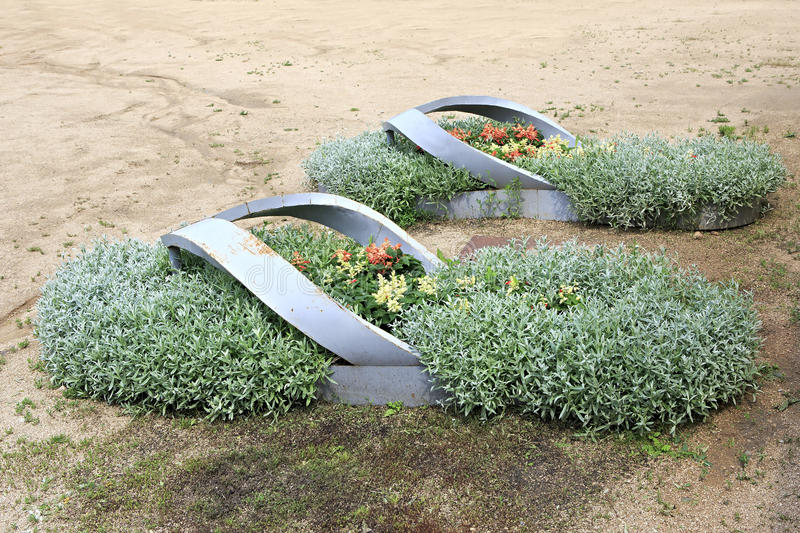 Iron bed in the form of sneakers in the Kennel Arboretum Blooming Valley. stock image