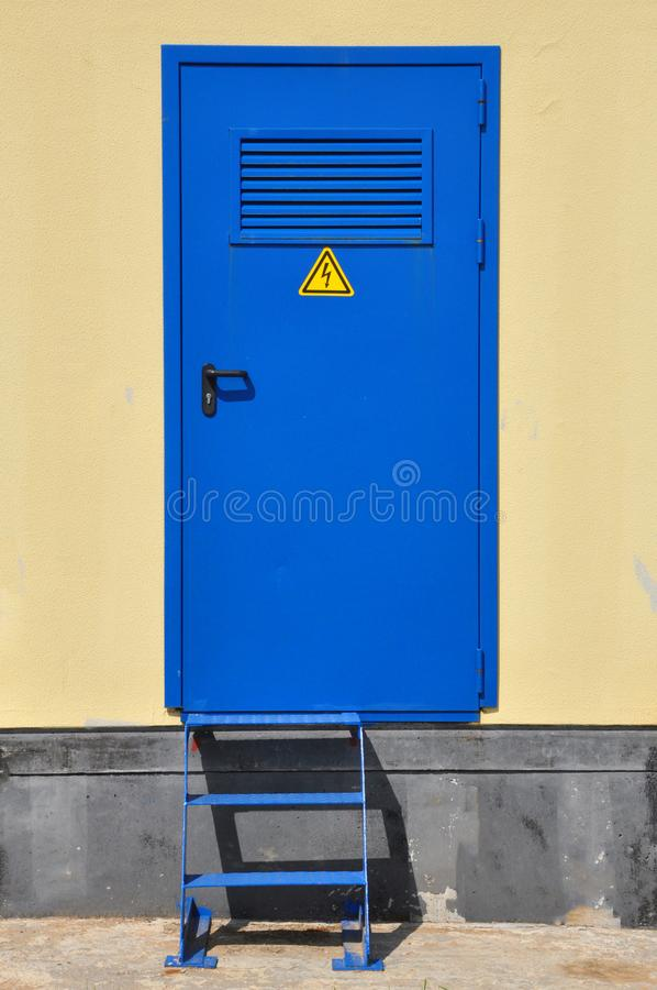 Iron blue door of a transformer box. Electricity, high voltage, do not enter the danger zone royalty free stock image