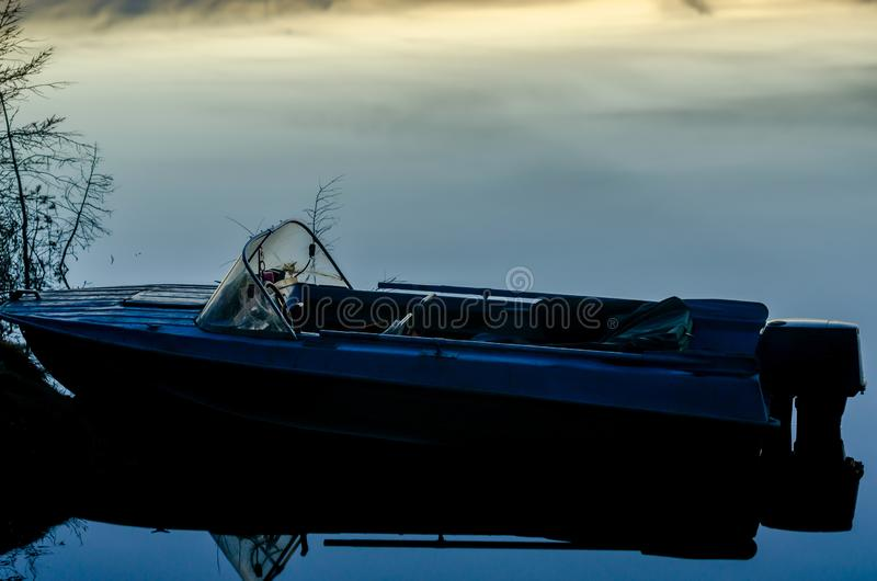 Iron boat stands on the pier against the background of smooth quiet water at night. Iron boat stands on the pier against the background of smooth quiet water at royalty free stock photo