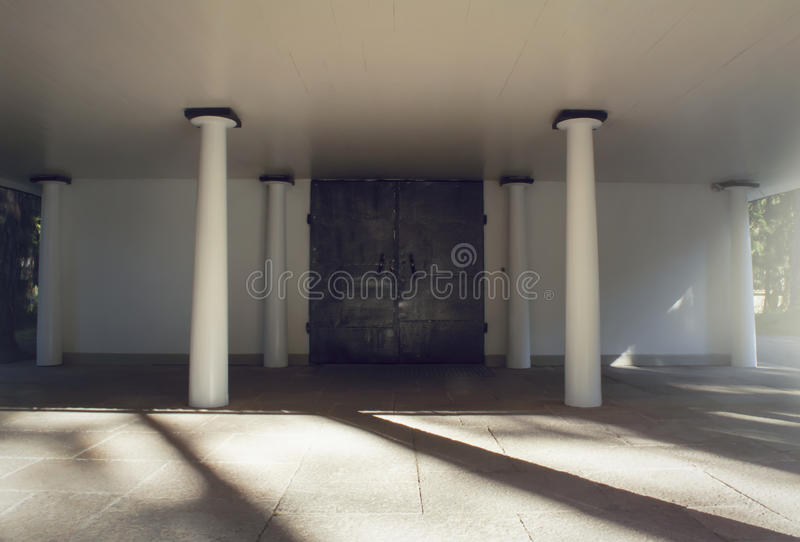 Iron cast doors and pillars before a cemetary crematorium and chapel. Iron cast heavy gates and pillars before a cemetary crematorium and chapel. Shadowplay stock photos