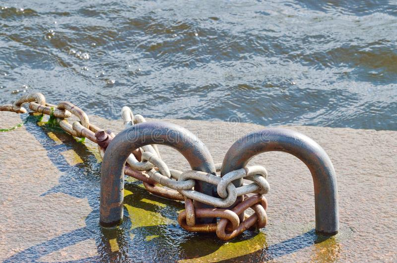 Iron chain on the pier of the river. royalty free stock photo