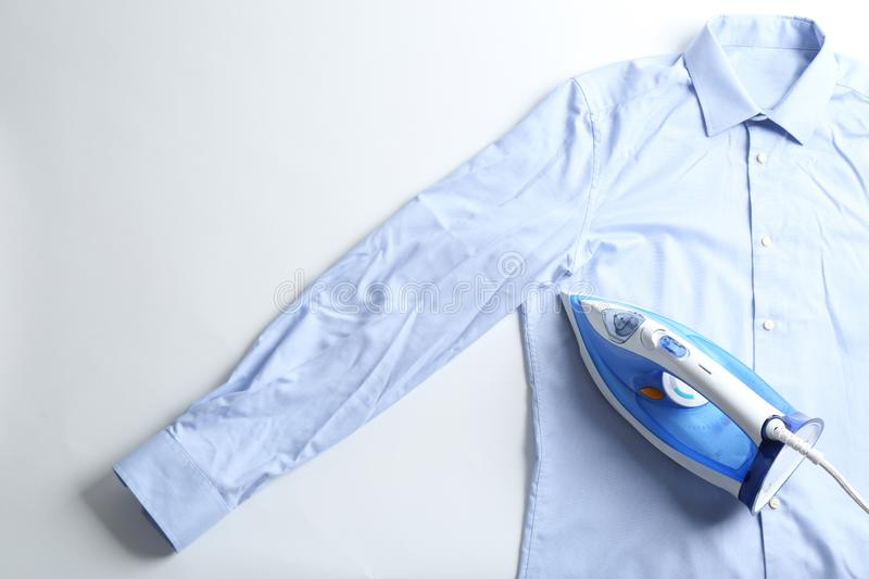 Iron with clean shirt on light background, top view. Space for text royalty free stock photography