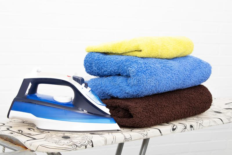 Iron with clothes. On the ironing board stock image