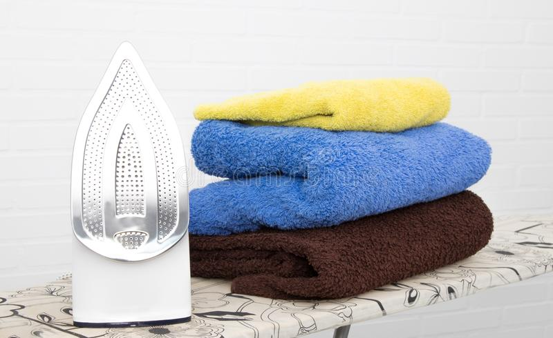 Iron with clothes. On the ironing board stock photo