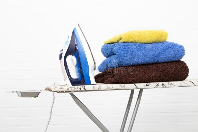 Iron with clothes on the ironing. Board stock images